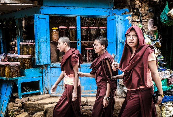 a photojournalist shot of three monks walking down a street