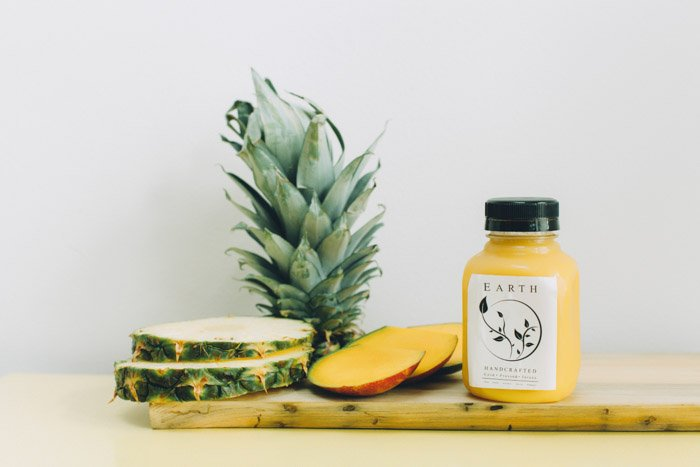 a product photography shot of a pineapple and product bottle on a wooden chopping board
