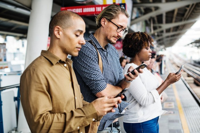 three people on smartphones standing outside an airport