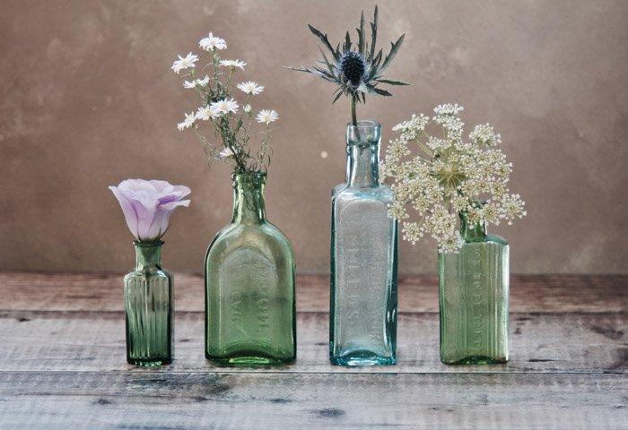 a still life of four glass bottles holding flowers
