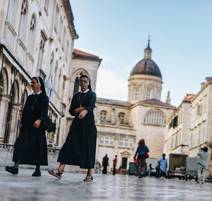 candid photos of two nuns walking through a busy square - street photography rights