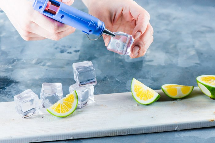 Set up for water splash photography with acrylic ice cubes, limes and glue gun