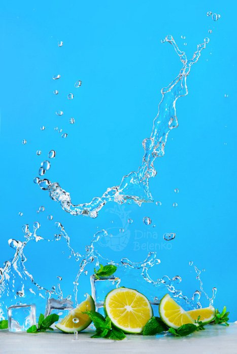 Lime slice, ice, mint leaves and a dynamic water splash of mojito or lemonade on a bright blue background. Refreshing summer drink concept with copy space.