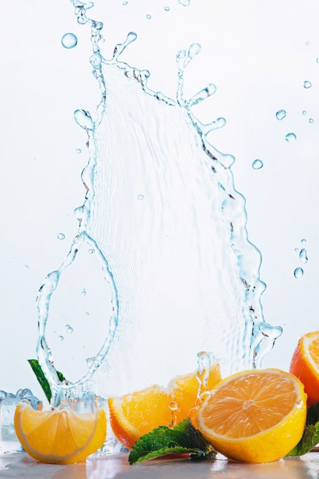 A fun food photography shot of oranges with cool water splash photography frozen above