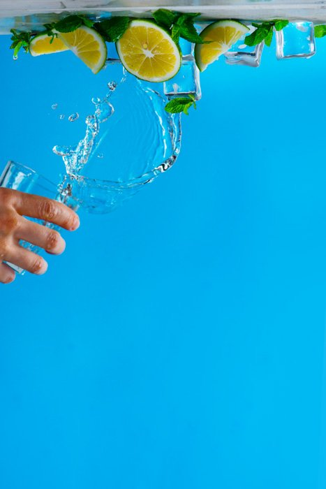 Upside down shot of poruring water onto a still life on blue background