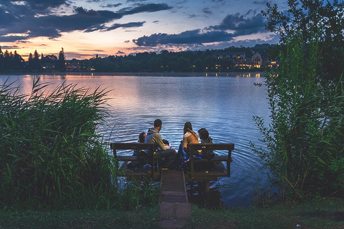 Photo of a family sitting beside a lake at sunset