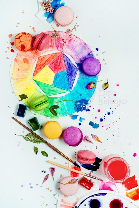 A birds eye view still life with colored macaroons, paintbrushes and leaves on painted surface