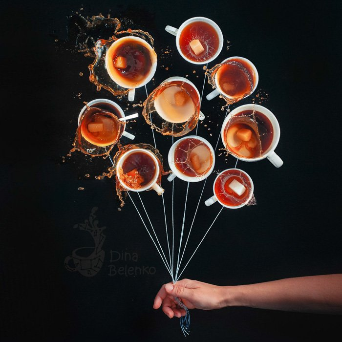 A creativestill life with 10 cups of coffee arranged in a circle with strings attached and a persons hand holding the strings as if it was a bunch of balloons