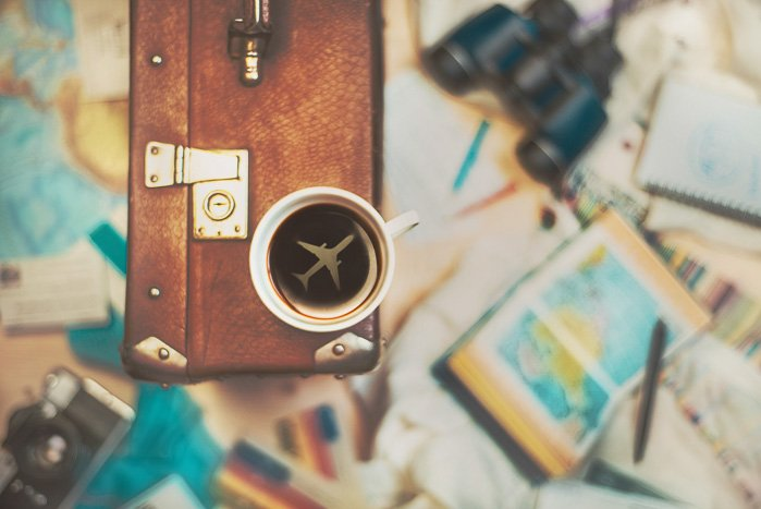 A travel themed still life with a cup of coffee perched on a suitcase with the shape of an airplane inside