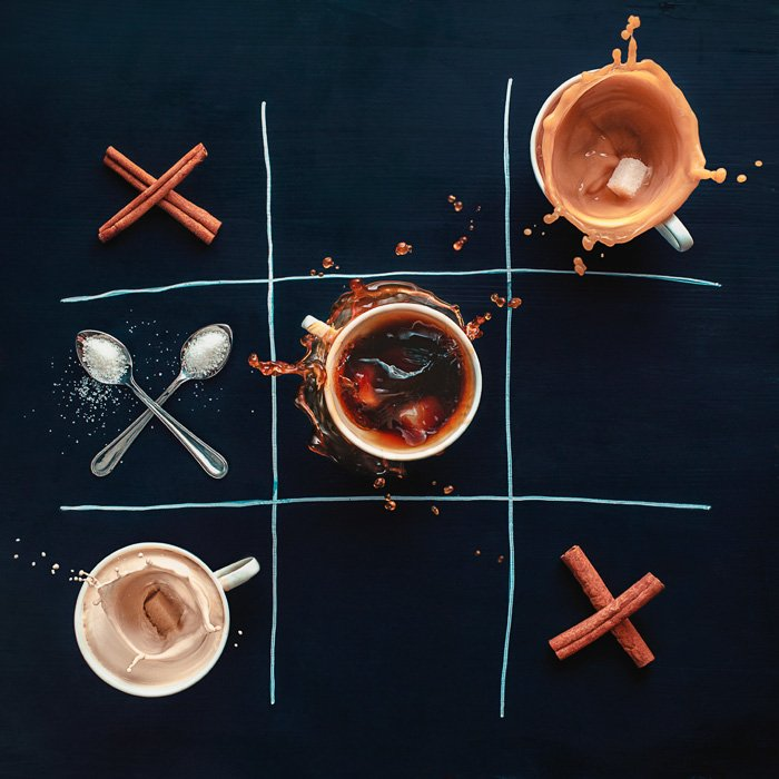 A creativestill life with cups of coffee, cinnamon sticks and spoons arranged in a tic tac toe grid