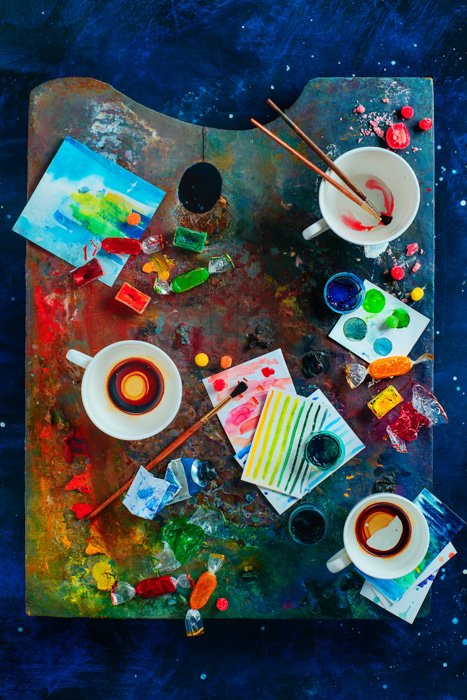 A bright artistic themed still life with a painters palette covered with paint, cups, paintbrushes and other art materials