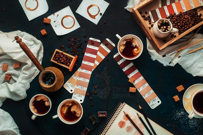 A barista themed still life with coffee cups, color charts and other brewing utensils