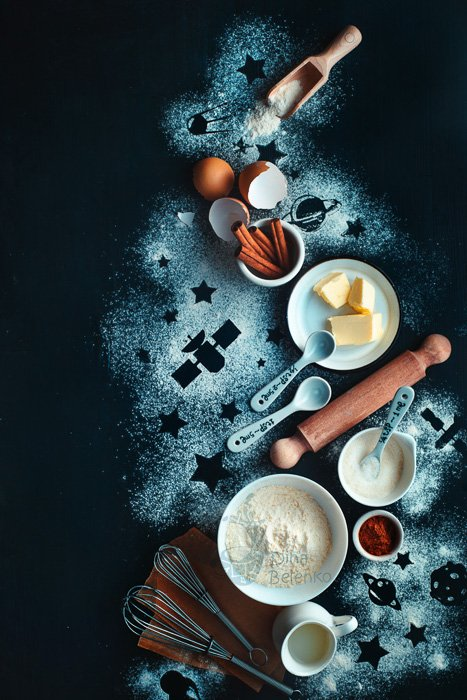 A dark and atmospheric food still life with flour, eggs, butter and cooking utensils on a dark surface