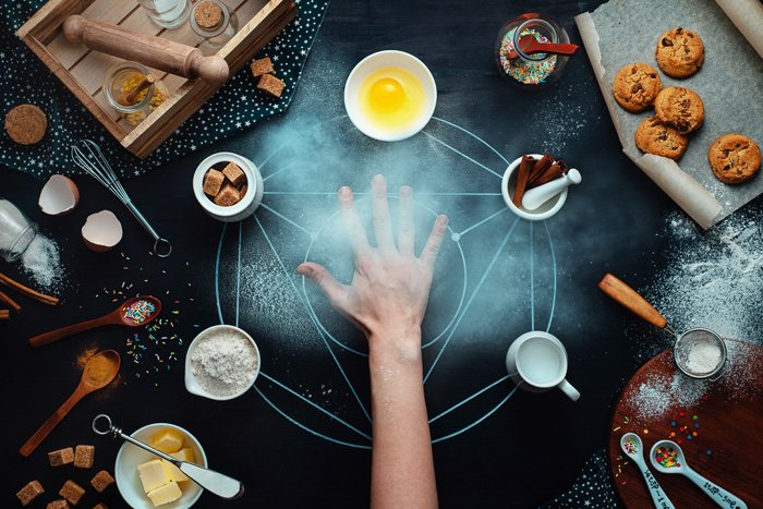 Occult themed food photography still life with a hand and food items on dark surface