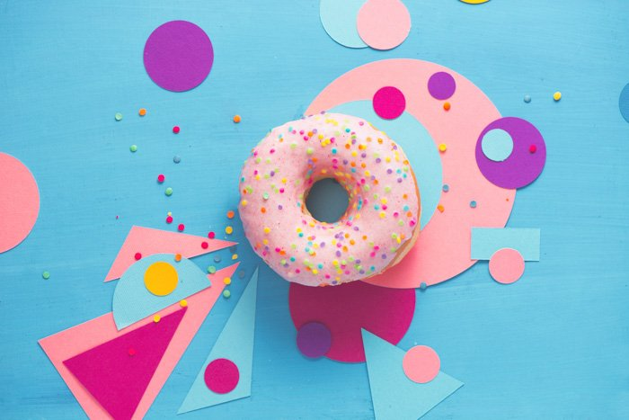 quirky flatlay of a pink doughnut on blue surface surrounded with pink paper