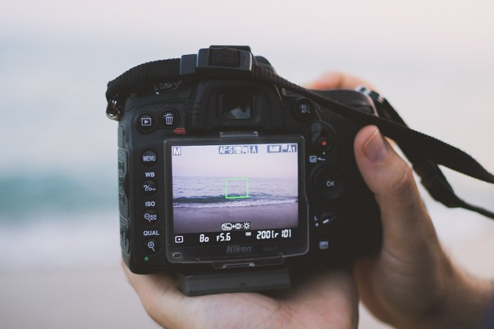 Close up of a person taking a photo of a seascape with a DSLR camera