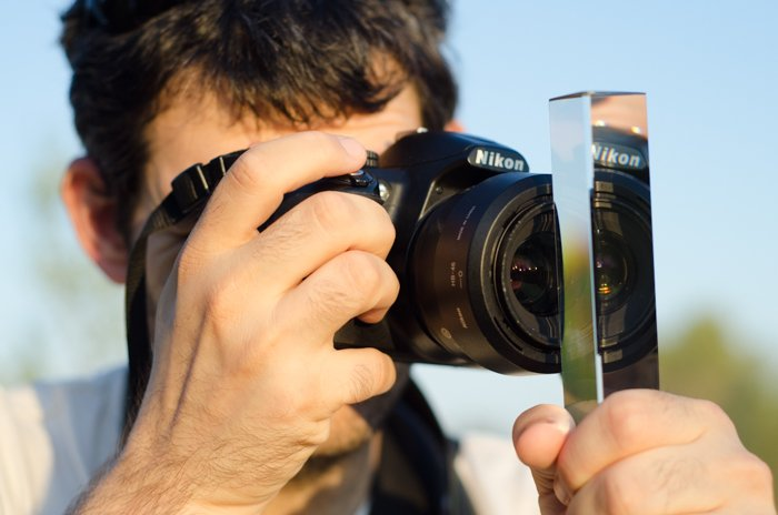 A photographer holding a photography prism in front of the lens of his canon DSLR