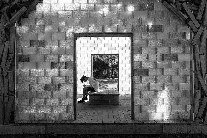 A black and white shot of a visitor in The Glass Pavilion 2017 by Gregor Kregar, street photography lighting