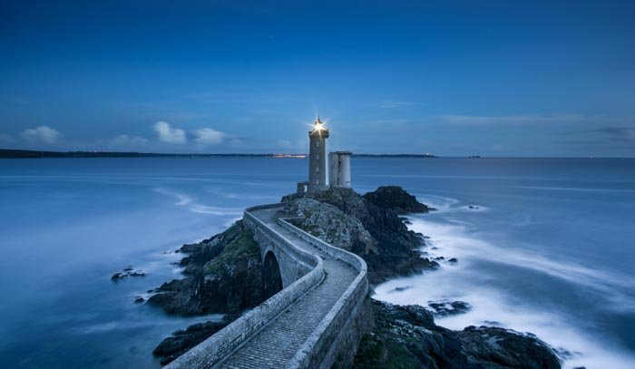 Landscape shot of a stone bridge leading to a lighthouse in low light