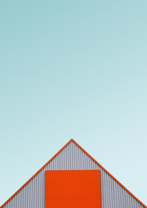 A photo of the orange roof of a warehouse or shed against a teal sky