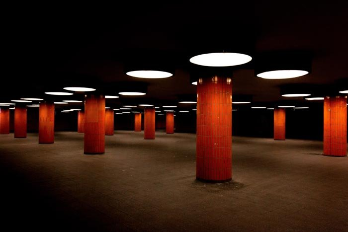 A photo of the interior facade of a dark room with many red columns