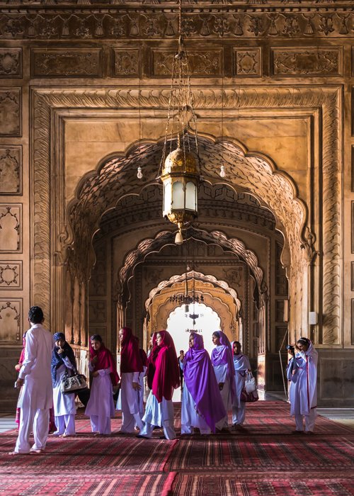 A group of people walking through Badshahi mosque in Lahore Pakistan