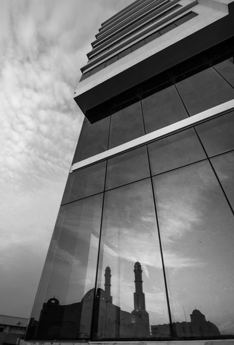 A buildings silhouette reflected in the glass facade of another building -- architecture photography composition