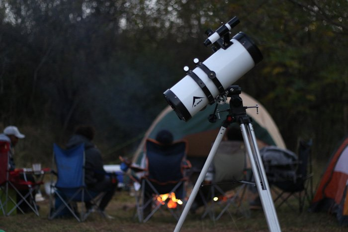 A telescope in the foreground of a campsite