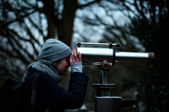 A girl in a grey hat looking through a telescope