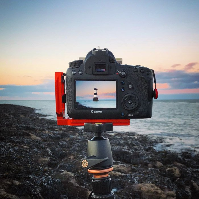 A DSLR camera on a tripod pointed at a lighthouse in a coastal area