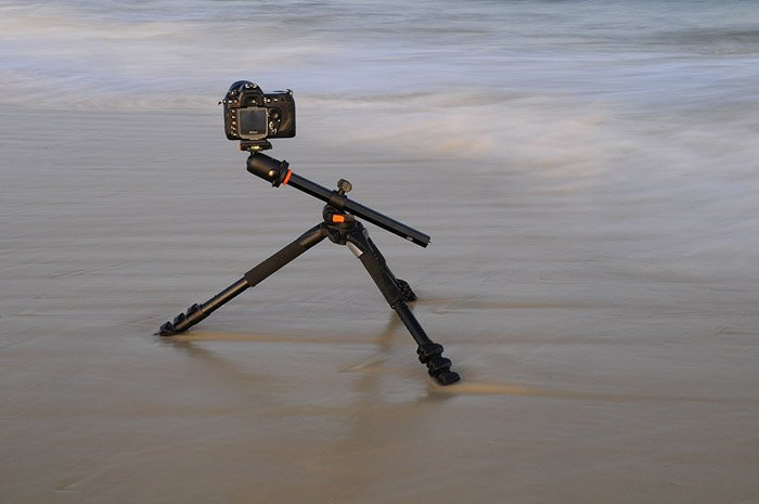 A DSLR camera mounted on a Vanguard Alta Pro 263AB 100 tripod on a beach