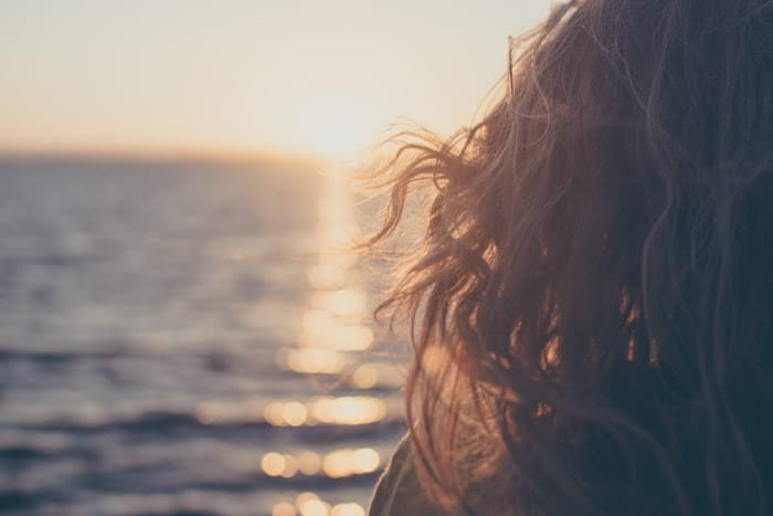 Dreamy portrait photo of a girl looking towards the sea at evening time