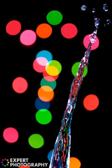 A water splash surrounded by colorful bokeh lights on black background