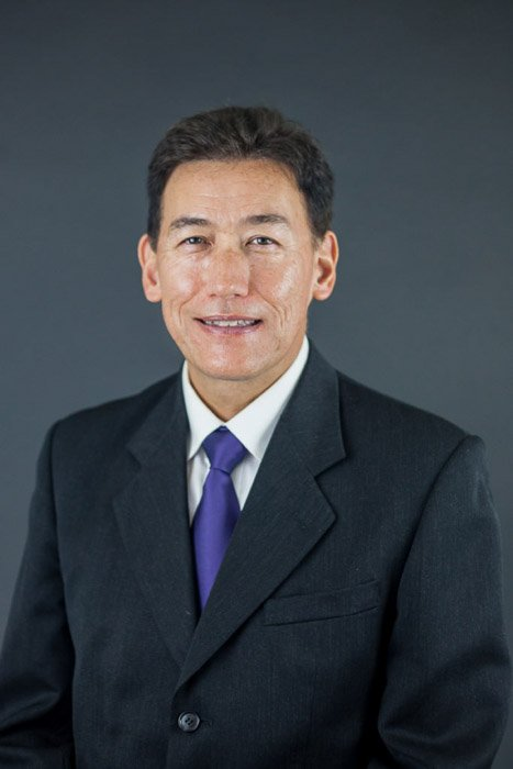 A corporate headshot of a man in a business suit against a plain grey background