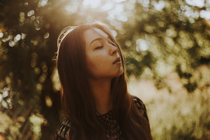 Atmospheric outdoor portrait of a female model using ambient light from the golden hour