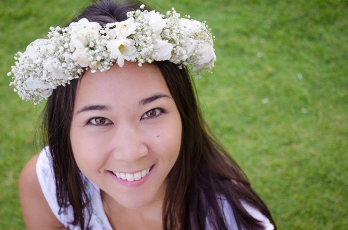 close up of woman wearing a flower crown looking up and smiling