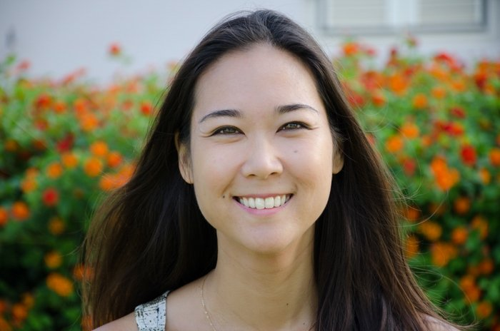 Headshot of smiling asian woman in a field of red flowers