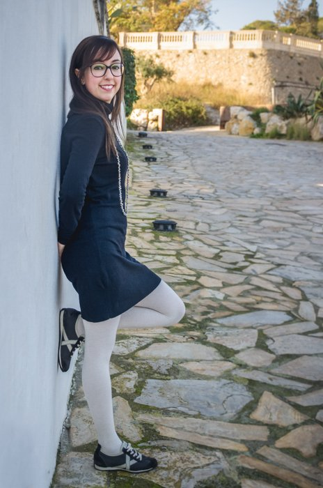 bespectacled lady in a navy dress and white stockings leaning against a white wall outdoors