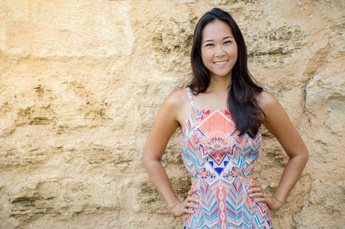 smiling asian woman in pastel geometric patterned dress standing in front of a big stone wall