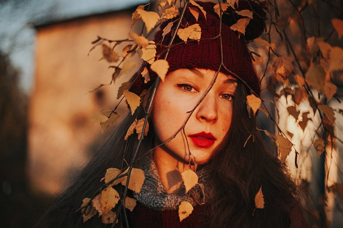 Beautiful close up portrait of a girl outdoors with tree branches in front of her face, shot using ambient lighting for a dreamy effect