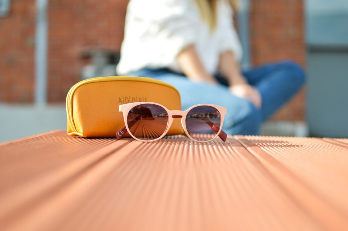 A product photo of sunglasses and case resting on a wooden table