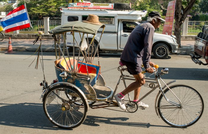A documentary photography shot of a samlar driver rising down the street
