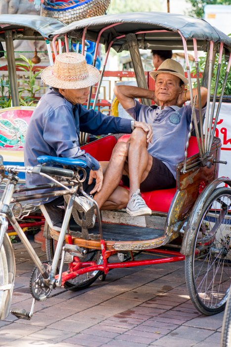 A documentary photography shot of two samlar drivers relaxing