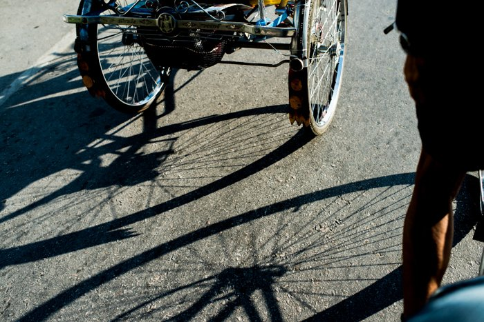 The shadows of bicycle wheels on the concrete road