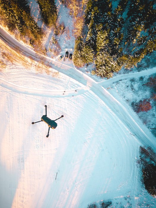 An aerial view of a drone flying over a snowy landscape