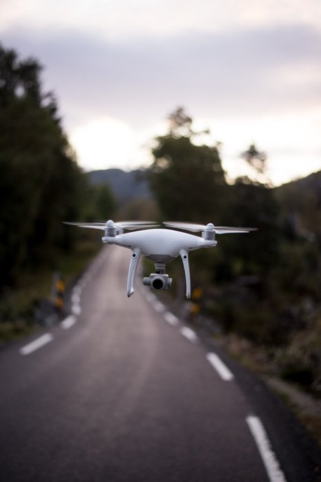 A white drone flying by a countryside roadway
