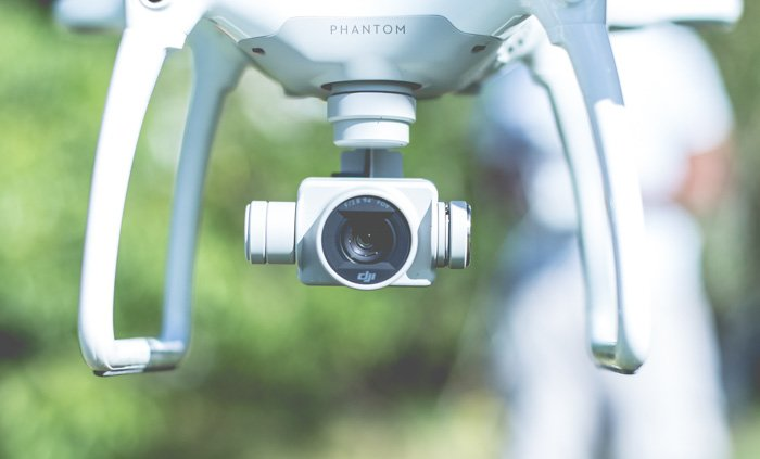 A close up of the camera of a white phantom drone in flight