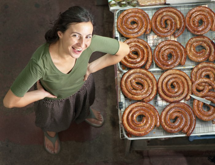 Young woman at a market in Chiang Mai, Thailand beside a stand selling Sai Oua - specialty northern Thai sausage.
