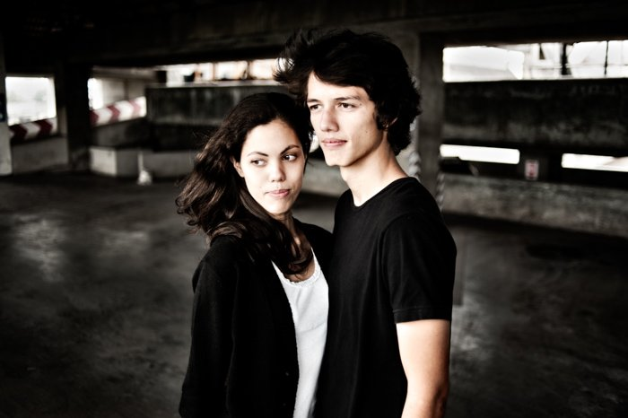An editorial portrait of young couple in an empty parking garage.