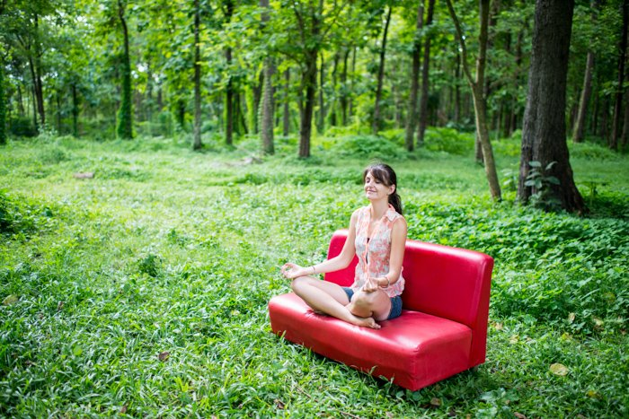 Woman sitting on a red couch in the forest meditating, nice example of editorial portrait photography.